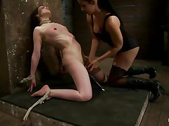 This is hawt and only gets better, a dominating milf wearing stockings and sexy clothing is showing a younger gal who's the boss. She ties her with rope and as the rope goes throughout those her pussy lips, a weight at the end of the rope makes things more interesting. The chick is suffocated too and probably she enjoys it a lot!