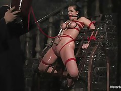 Mia Bangg is bound and gagged in the dungeon where her torturer sprays her nipple-clamped tits. He asks if she wants to get fucked and she does, but first he gives her a little greater amount pain by pulling tight the rope that splits her pussy lips and smacks her pussy before using a dildo on her.