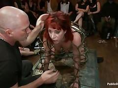 They've putted her in a special cage and as the bald man fucks her sexy mouth, 3 dirty strumpets are taking worthy care of her ass. She is fucked from both ends and the sex toy and fingering she's getting on her arse only makes her mouth want to swallow that dick as deep as she can while the public see her.