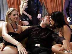 A blond and a dark brown are rubbing a guy's crotch whilst sitting on a couch. They pull out his cock and start to suck it, every awaiting her turn. Another dick enters the scene and the dark brown goes to blow it.