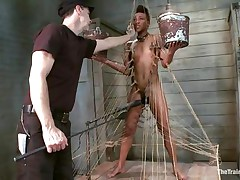 Nikki is all tied up and standing on her legs. Filled with clothespins and strings, she has to be careful and not to drop the two buckets she`s holding, while a large vibrator makes sensations on her soaked cunt. This babe gets all whipped for being such a bad ebon girl. Her executor will take very nice care of her!