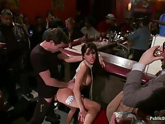 Gia DiMarco is on a rope leash, getting fucked in the wazoo right in the middle of the bar while the patrons watch. This babe continuously thanks James Deen for fucking her ass. Then she's on the floor, getting fingered by a woman, squirting all over. This babe mops up the mess with Gia's hair, then fists her.